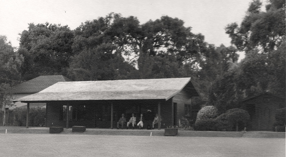 "Picture of the clubhouse as it appeared around 1955 with members sitting under the open front verandah. To the right can be seen the original 10 by 11 foot ""shed"" that served as a locker room. The building behind the clubhouse to the left is the Gamble House carriage house."