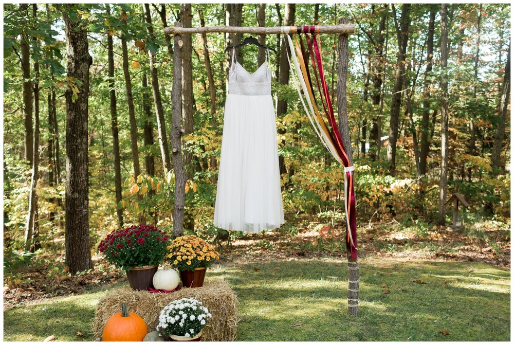 Bridal dress hanging on an outdoor ceremony space for a fall elopement in Virginia