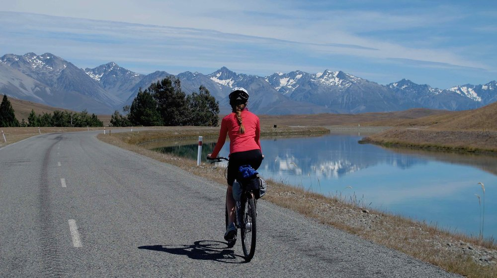 Exploring regions by bike will take you away from the crowds, into untouched areas you have never imagined! - Our editor riding on the Alps to Ocean cycle trail in New Zealand from Lake Tekapo to Twizel with Mt Aoraki on the right.