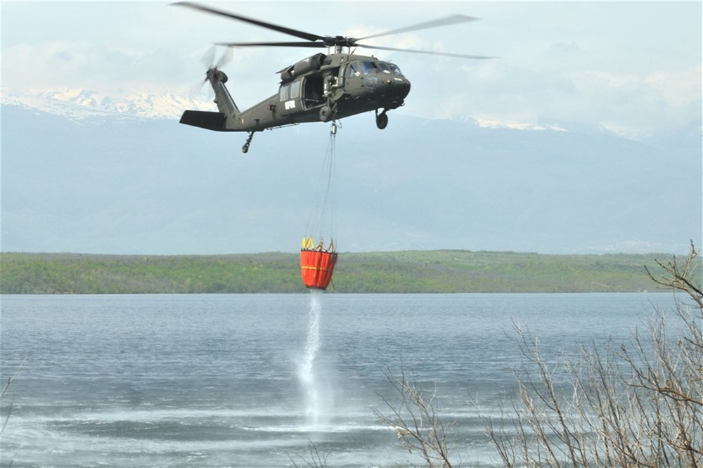 A flight crew from Multinational Battlegroupe East fills a Bambi Bucket. By Joshua Dobbs/U.S. Army. Public domain.
