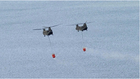 Two Japanese Ground Self-Defense Force helicopters hover over off Natori, Miyagi Prefecture as they carry seawaters to drop onto the tsunami-crippled Fukushima Dai-ichi nuclear plant Thursday, March 17, 2011. (The Yomiuri Shimbun / Kenji Shimizu)