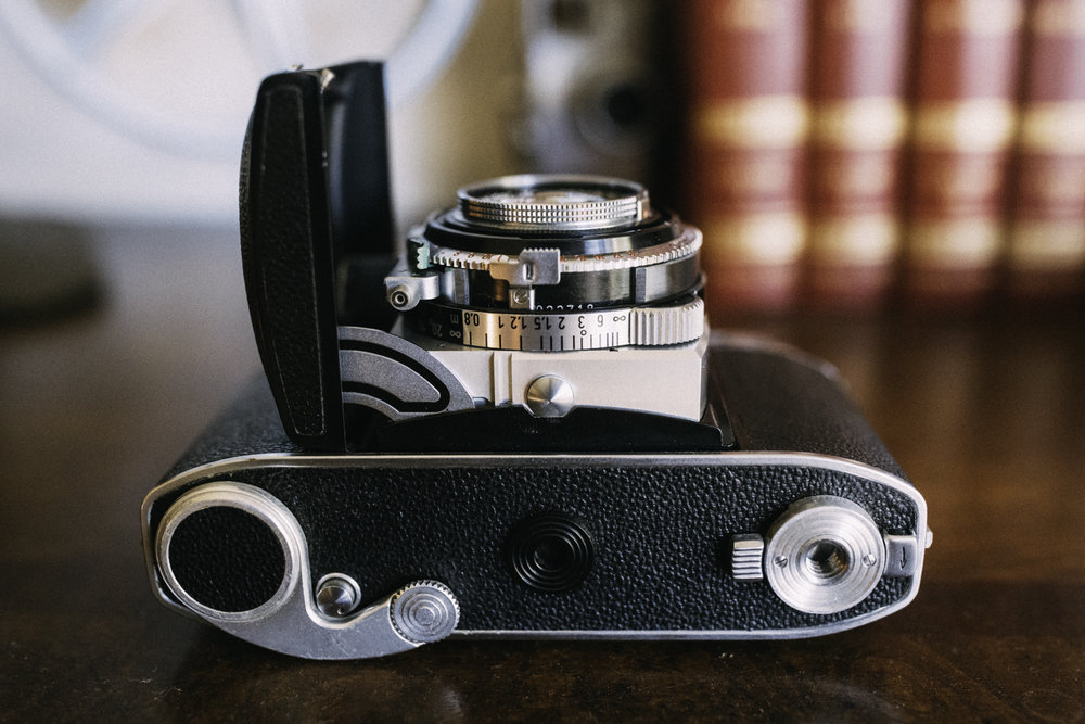 "Here's the camera bottom. From left to right, we have the film advance lever, a connector for a special flash unit for the camera, and the twisting lock for the film door, which surrounds the 1/4"" mounting point."