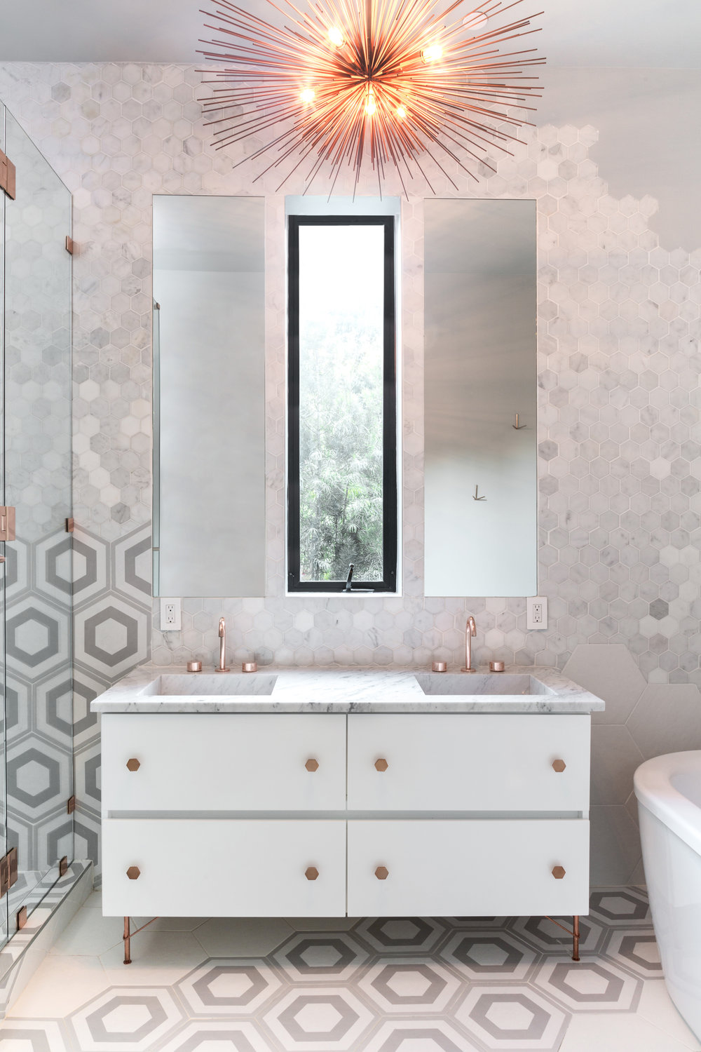 Middle Bathroom - ∙unique tile +Masonry∙bespoke Copper Hardware∙Maximal minimalismSituated between Bedrooms Two and Three, this regal bathroom features Brodware minimalist copper faucetsimported from Australia, polished copper hardware,flawlessly carved marble trough sinks, whimsically unique hexagonal tile work, and a made-to-order urchin chandelier. Luxuriating in this airy bathroom is sure to make anyone feel like a star.