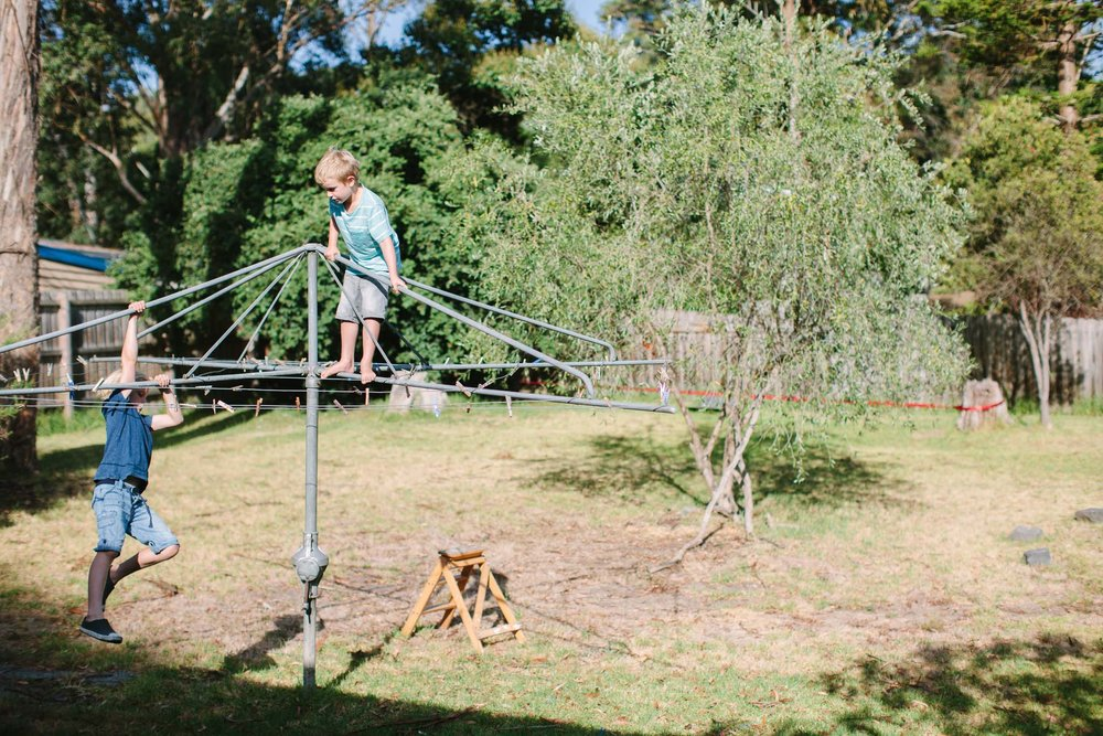 Two boys playing on the clothes line