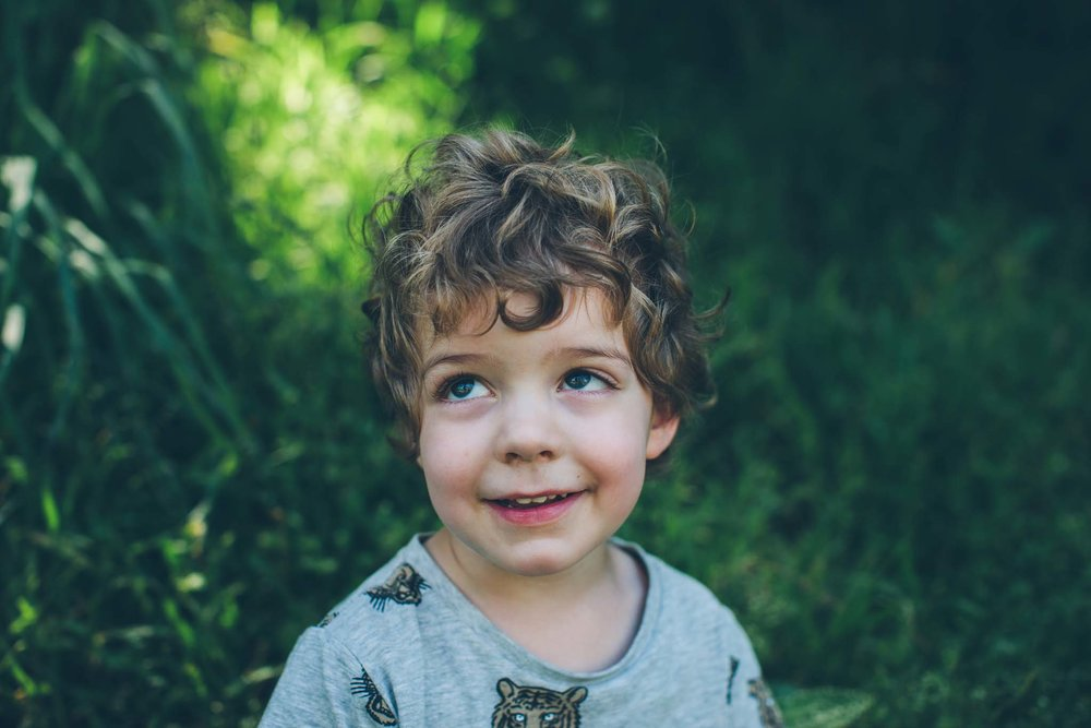 Boy smiling off-camera in a professional outdoor shot