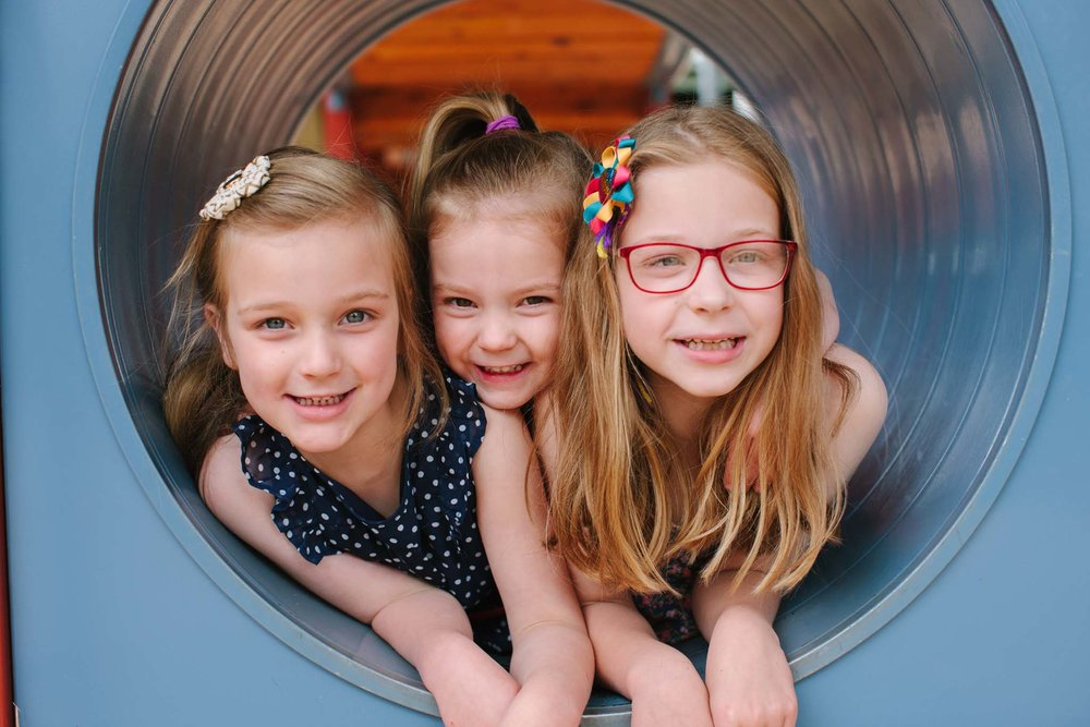 Three sisters in a playground tunnel