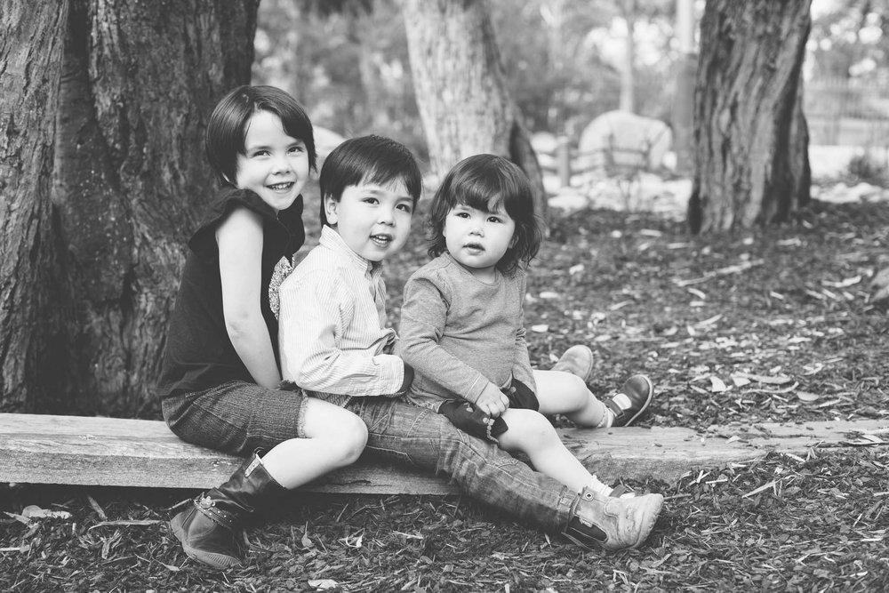 Three kids sitting on a log in the bush