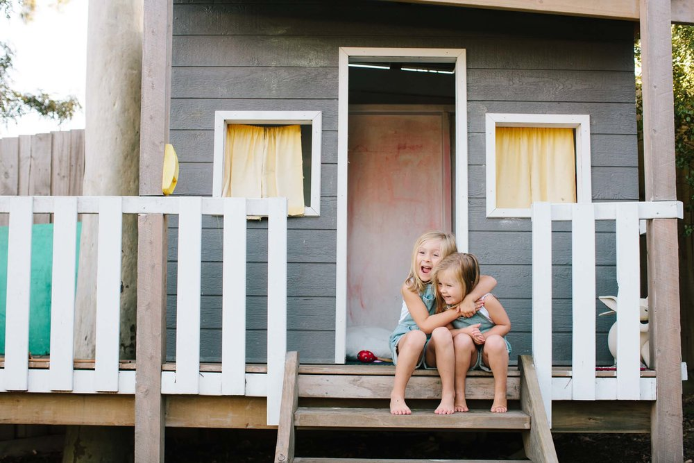 Two kids hugging on the cubbyhouse steps