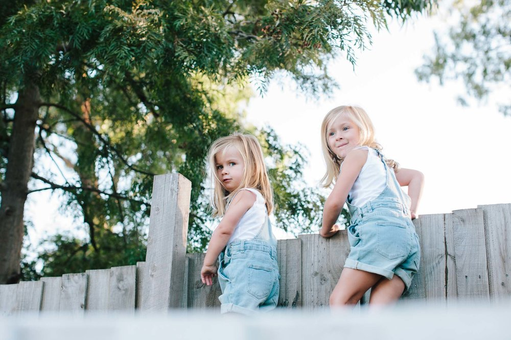 Two girls climbing along a tall fence