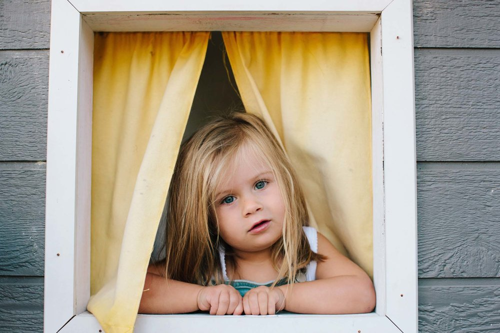 Girl peeping through cubbyhouse window