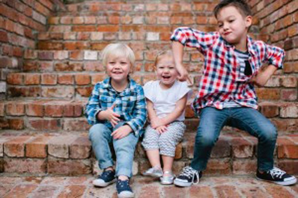 Brothers and their little sister playing on steps