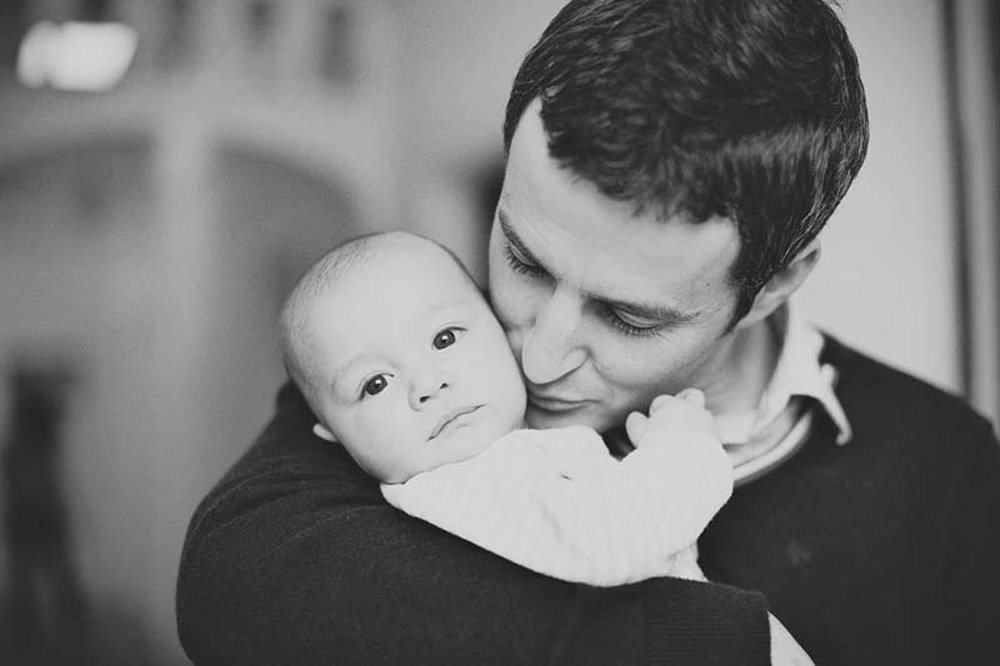 Father kissing baby in greyscale