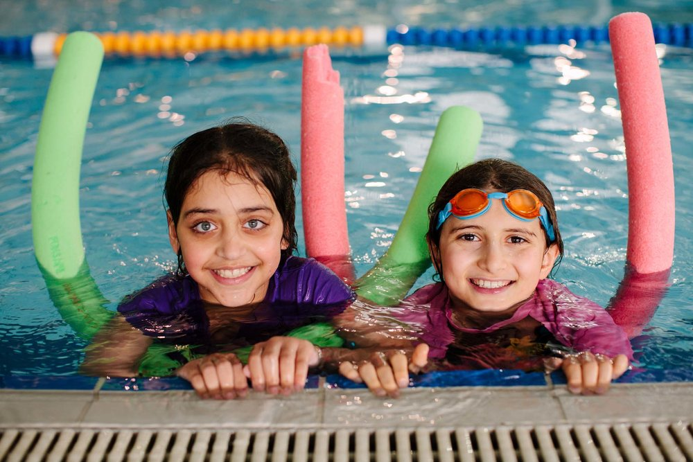 Kids in pool pose in swimming lesson advert
