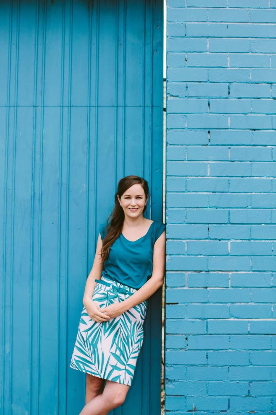 Smiling brunette woman leans against blue building