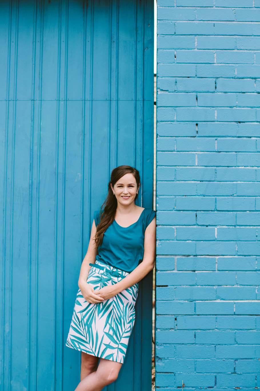 Smiling brunette woman leans against blue building