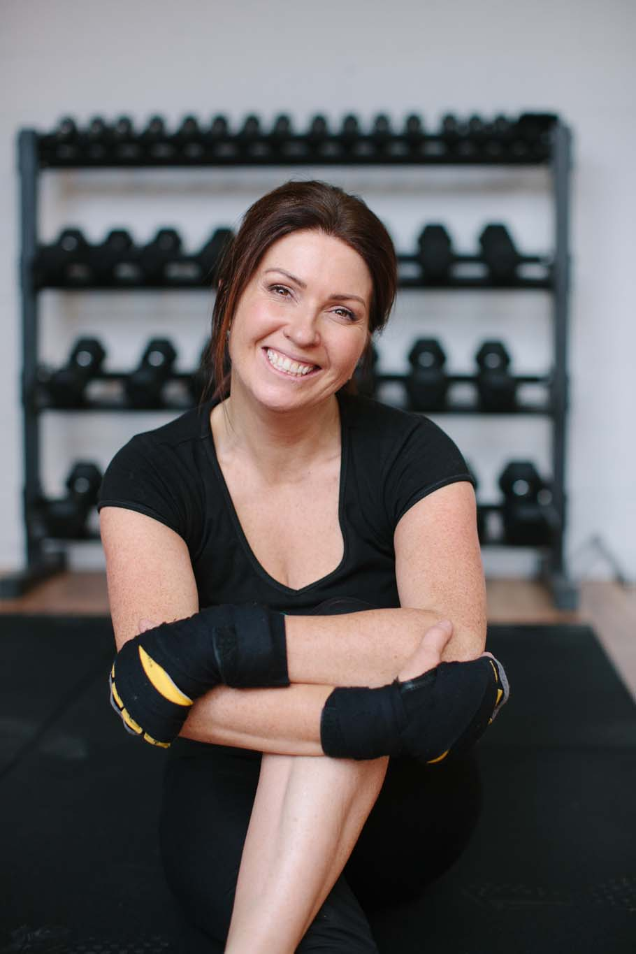 Corporate photo of woman with dumbbell backing wall