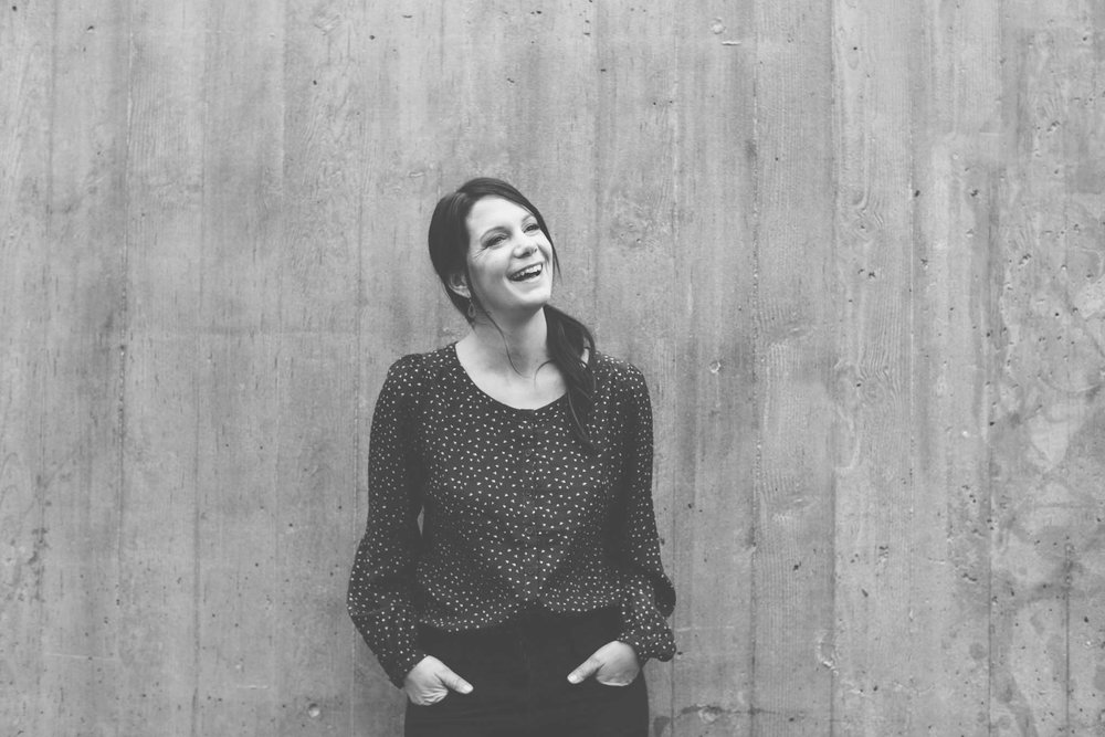 Smiling woman in businesswear against wood panles