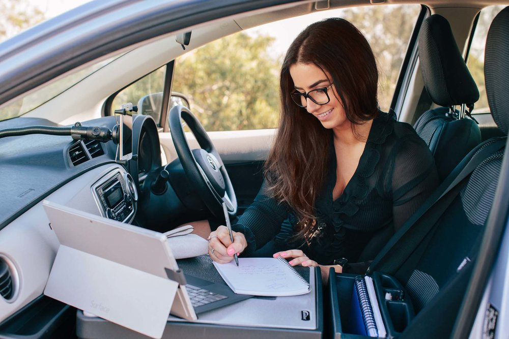 Woman working on-the-go in her car