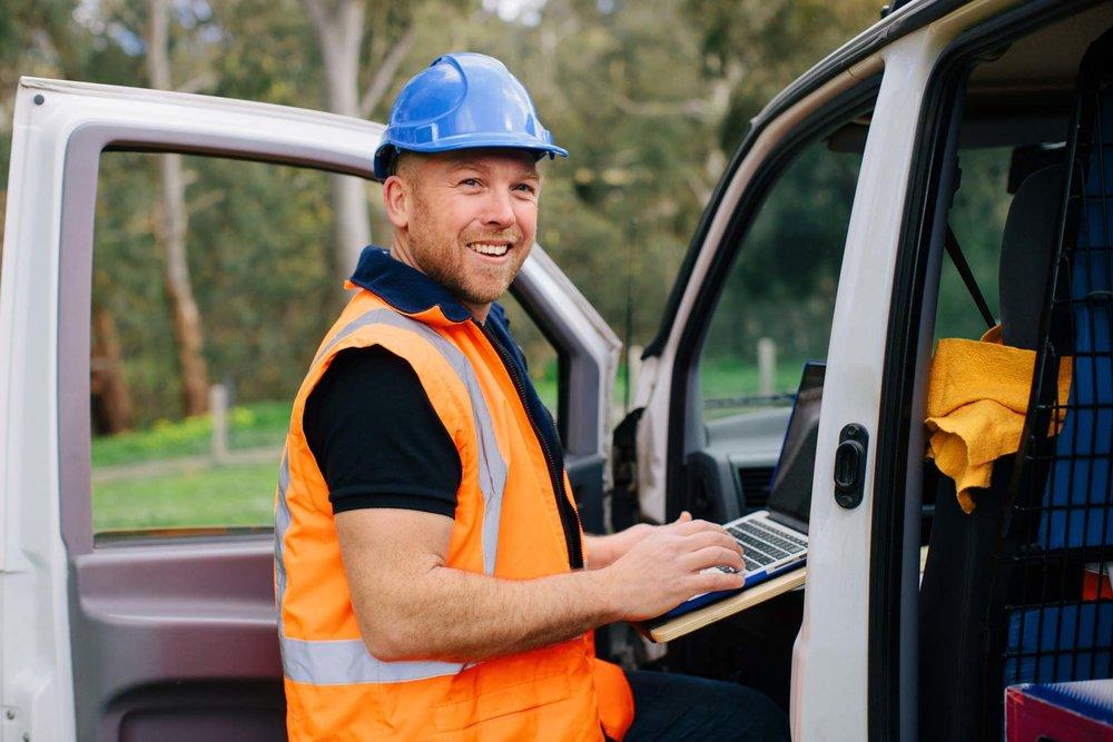 Tradesman in bright vest takes notes