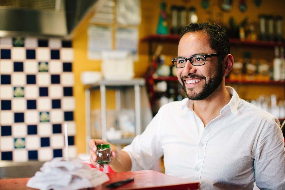 Man smiles at conversation partner at coffee shop