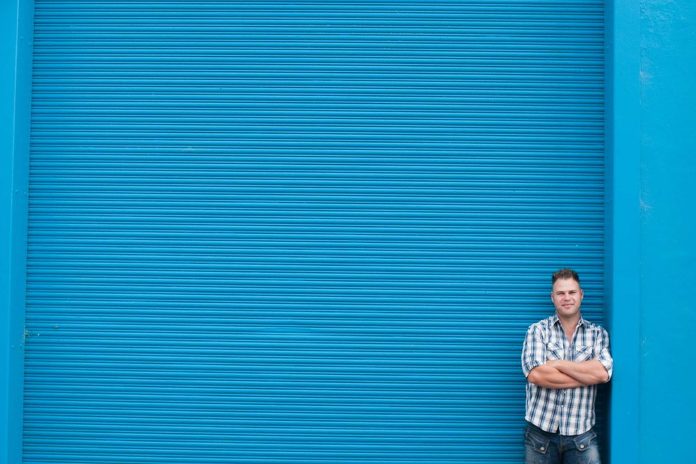 Man in plaid shirt poses against contrasting blue roller