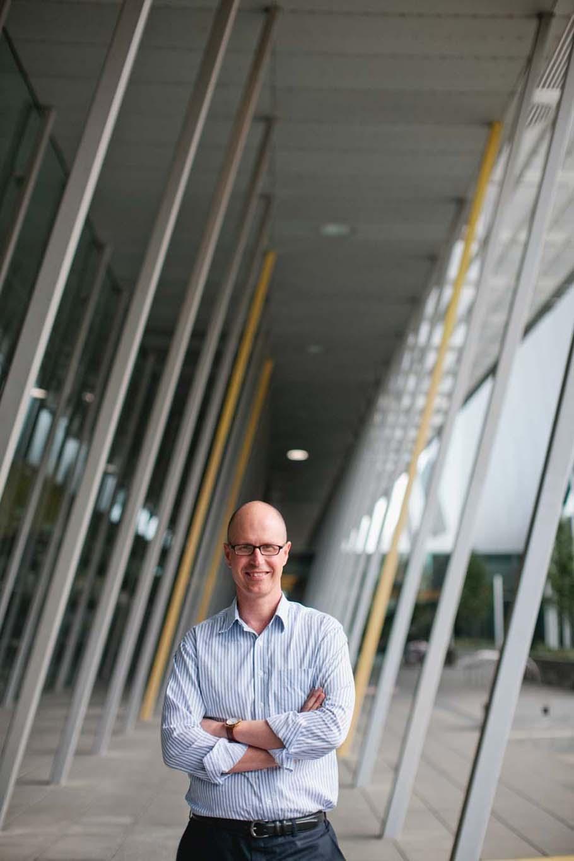 Man poses at an angle to pillars behind him