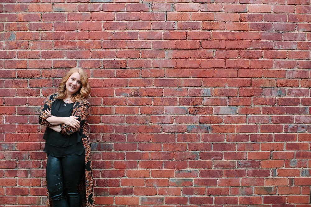 Smiling woman poses against brick wall