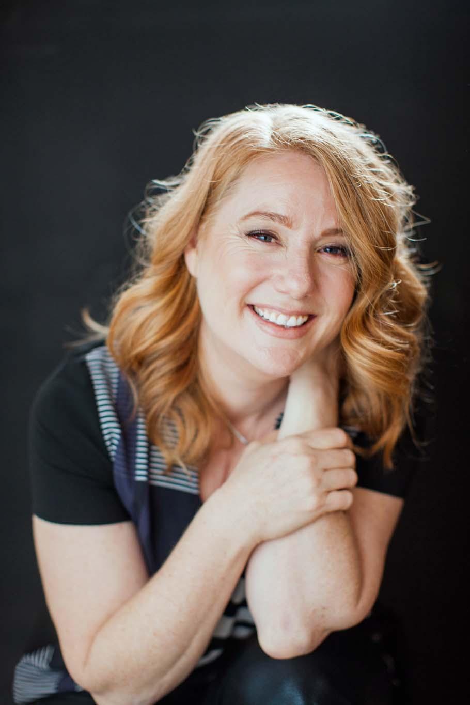 Woman smiles warmly in a photo studio portrait
