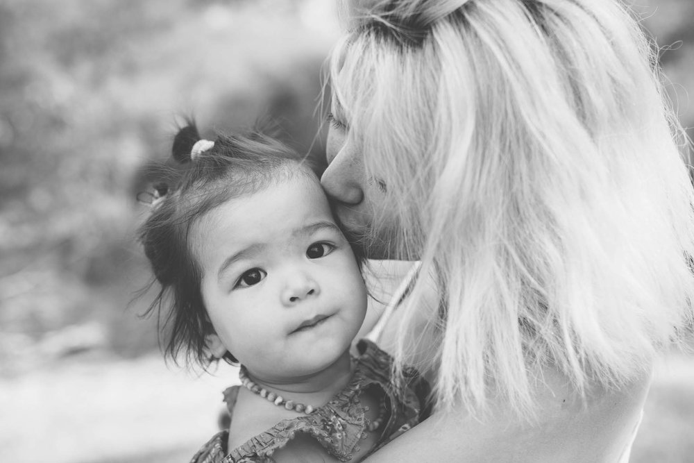 mother kissing daughter in greyscale