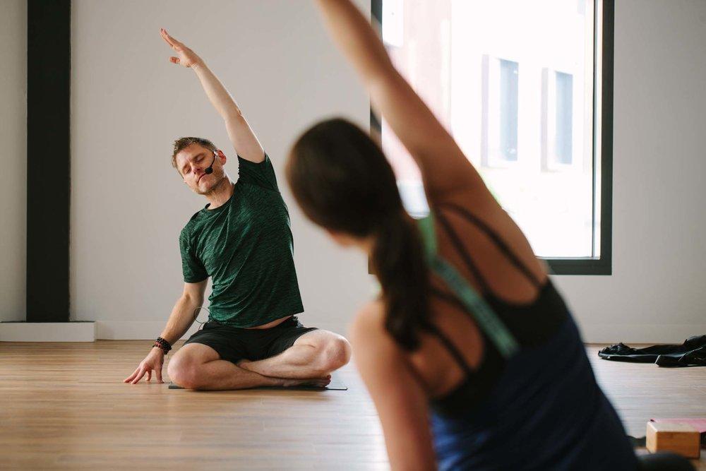 Yogi wearing headset demonstrates movements to class