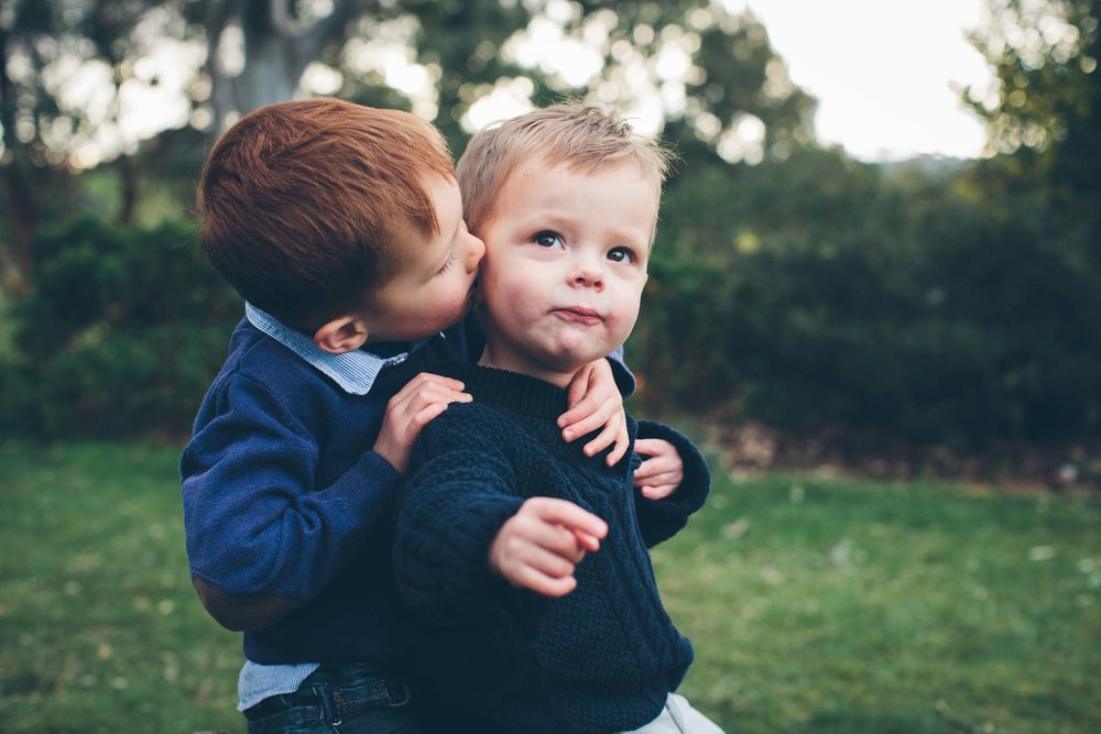 Little brother in blue gets a kiss