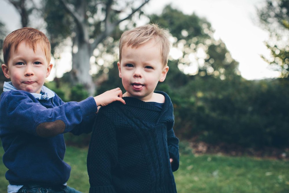 Boy in blue pokes out his tongue with his brother