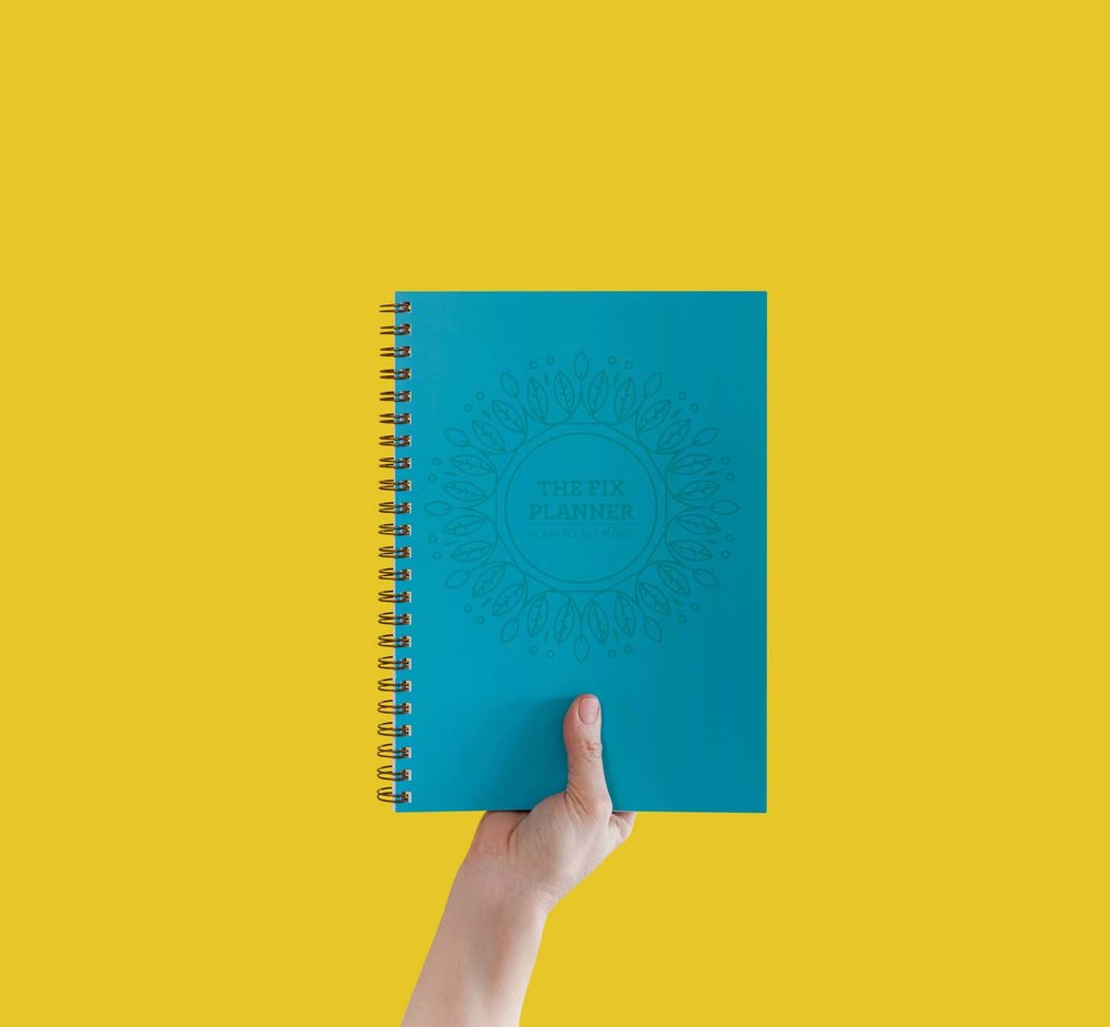 Hand holding blue spiral notepad against contrasting yellow backdrop