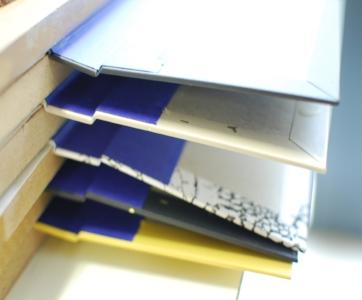 L'emboîtage ou le début d'une reliure complète - Vous apprendrez à façonner 5 cahiers de 5 feuillets et vous utiliserez la couture copte pour les relier entre eux. Vous collerez une mousseline sur le dos des cahiers pour préparer la phase d'emboîtage. Vous apprendrez à façonner la couverture rigide en toile et emboîter le corps d'ouvrage : encoller proprement la première et la dernière page de garde pour associer les deux parties du livre.