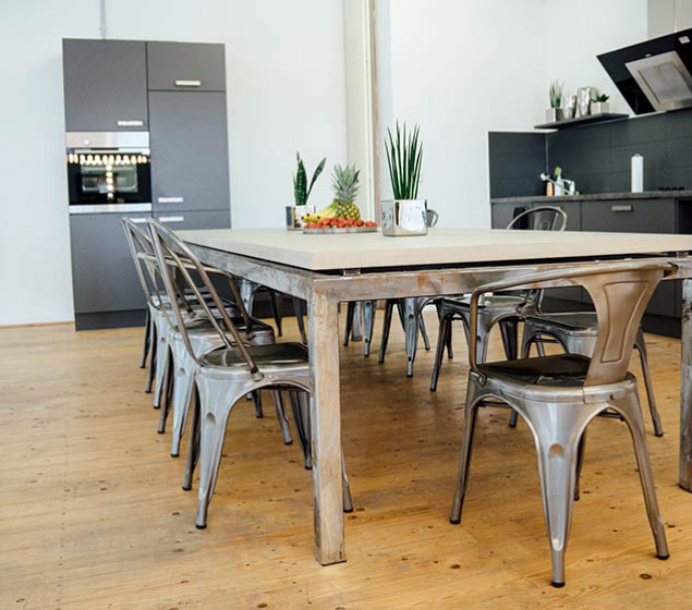 Großer Besprechungstisch in offener Küche