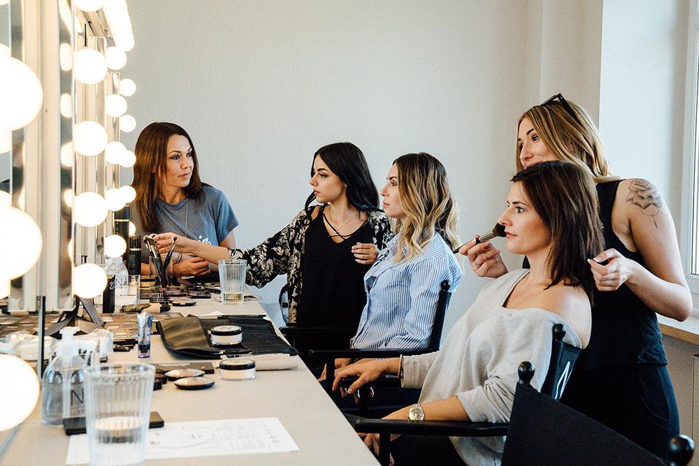 Make-up Artist und Dozentin NANE mit Schülerinnen vor der Spiegelwand