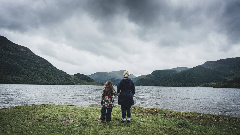Family look to the water in the Lake District, UK