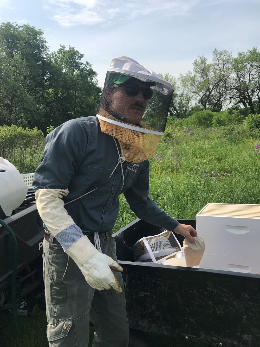 College of DuPage Prairie Manager Remic Ensweiler prepares to visit and maintain the four bee hives on the eastern edge of the COD campus