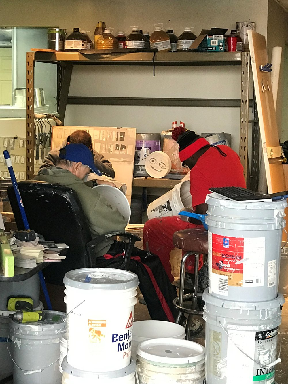 Workers from the Little City program for people with intellectual and developmental disabilities scrape dry paint from used five-gallon buckets. The non-profit is reducing waste going to landfills and helping to employ people with special needs.