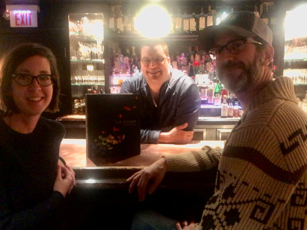 "Sarah Hemberger, Micah Melton, and Allen Hemberger (left to right) collaborated for more than two years to create ""The Aviary Cocktail Book."" The massive book (center) is one part coffee table book, one part cook book."