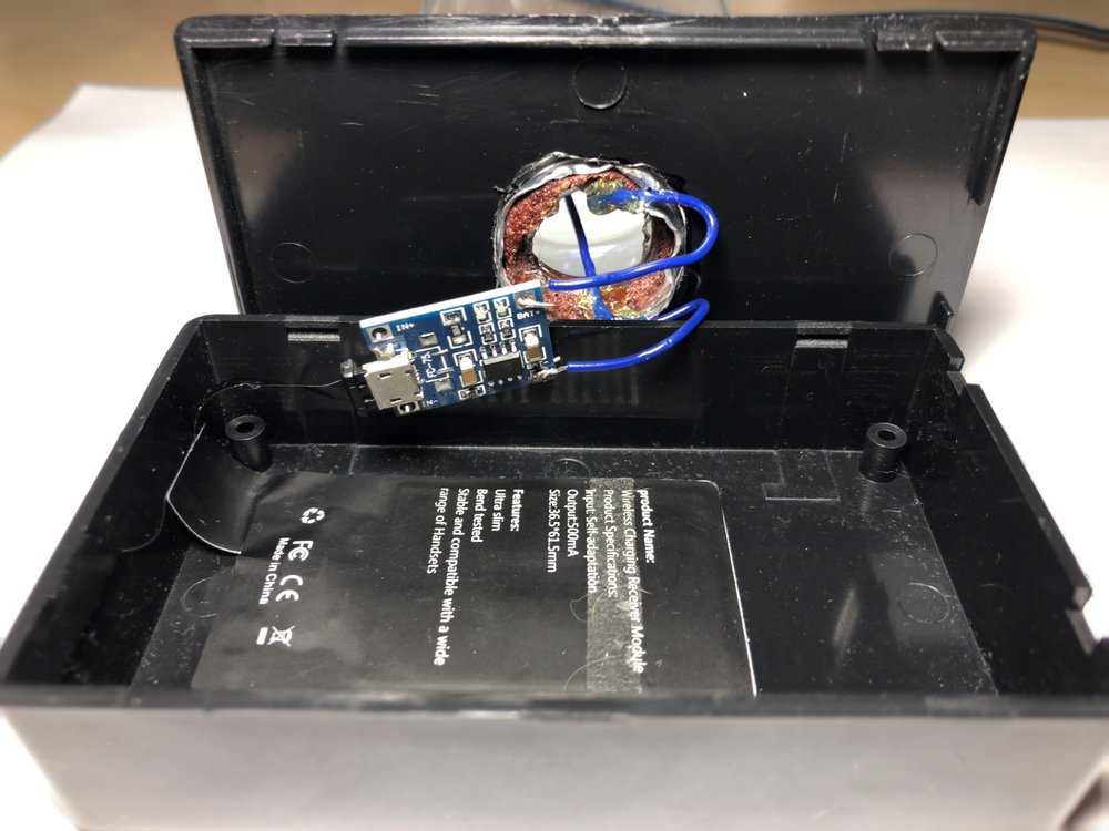 Figure 7:  Project box after using a rotary tool to create a hole for the light bulb base. This photo also shows the TP4056 soldered to the LED leads, and the Qi charging pad as well.