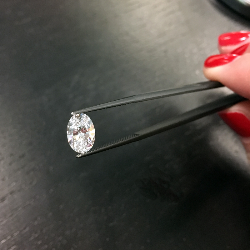 loose lab grown oval diamond in tweezers