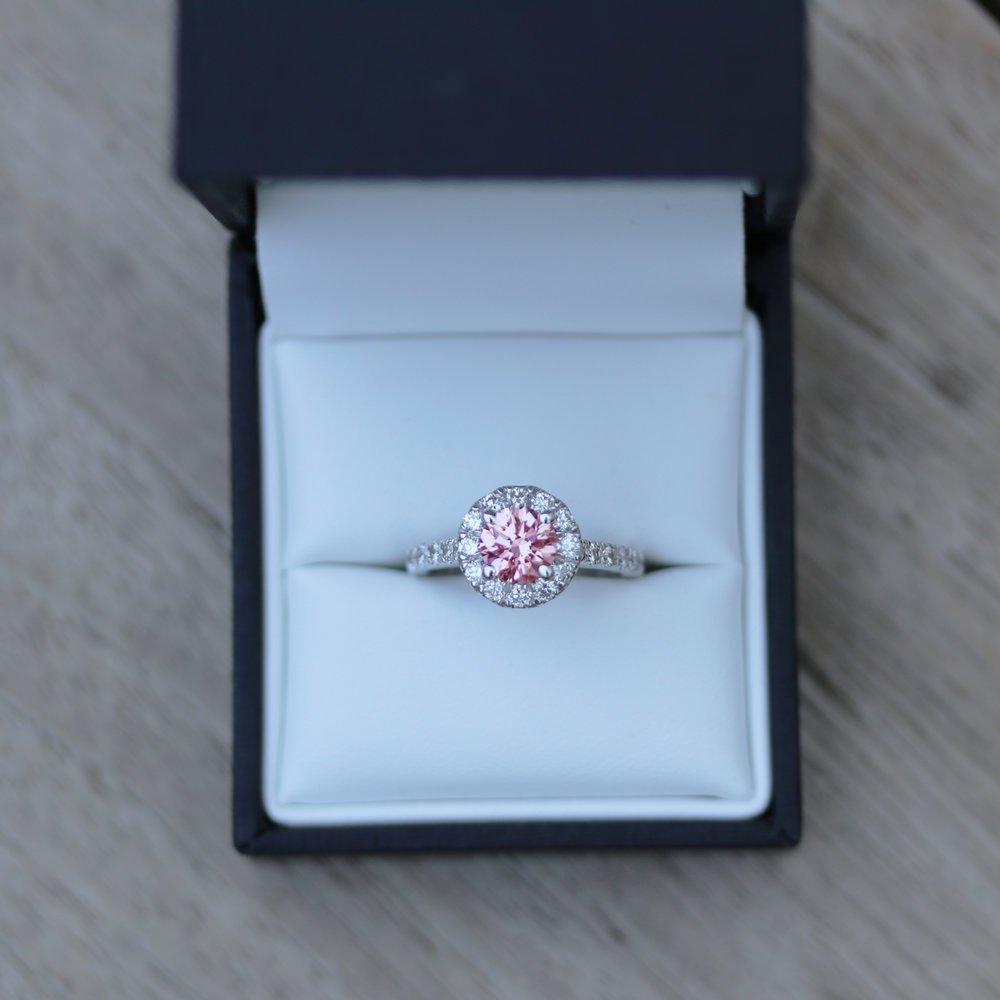 fancy pink center stone lab diamond engagement ring with a diamond halo and diamonds down the band