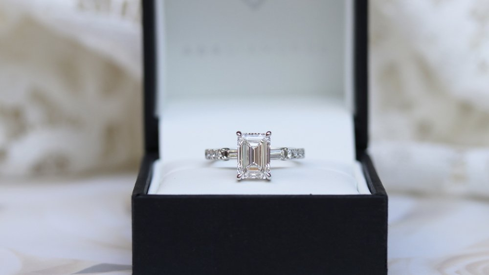 custom three stone emerald and baguette lab diamond engagement ring with diamonds down the band
