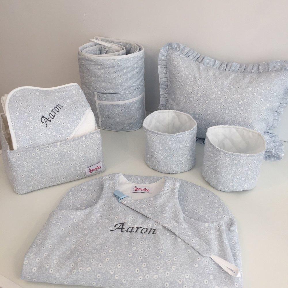 Idée de coffret naissance complet: gigoteuse, panier à couches, panier à accessoires, attache-tétine, coussin, tour de lit et serviette.