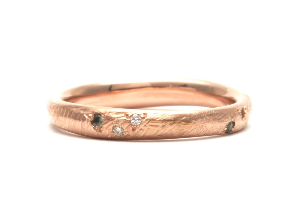 Golden Path Ring -  18 carat rose gold ring to sit alongside another ring set with a pool like sapphire. The line of the ring undulates to fit in with the other, with a rocky, sandy texture scattered with green sapphires and white and champagne diamonds.