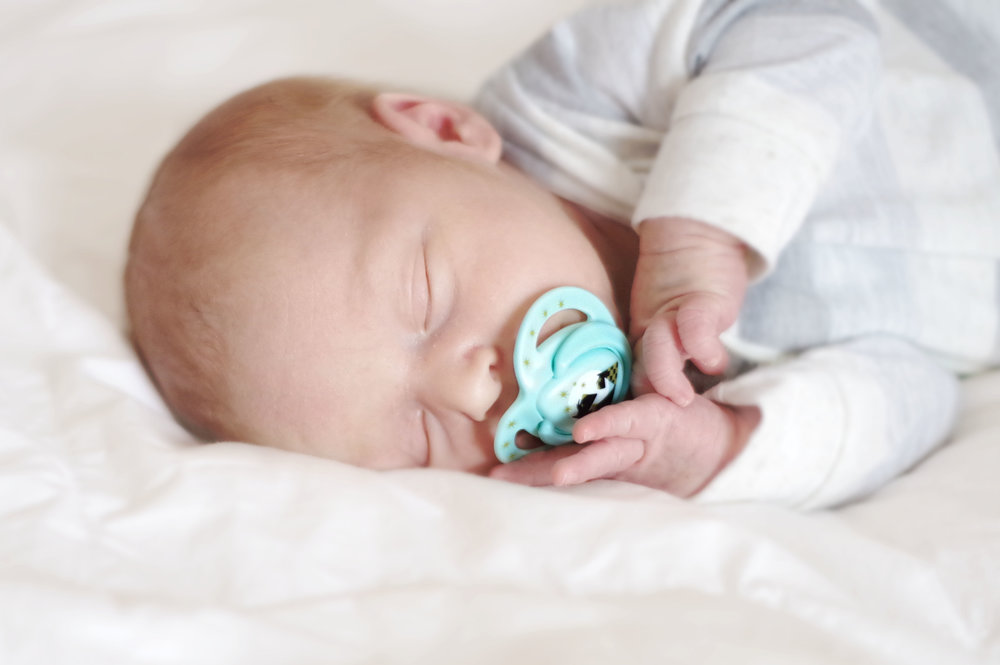 baby with soother on bed  belleville family photographer
