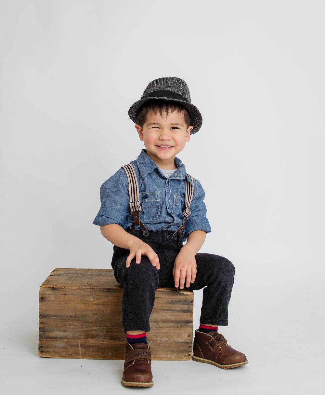 boy in studio sitting on box  belleville family photographer