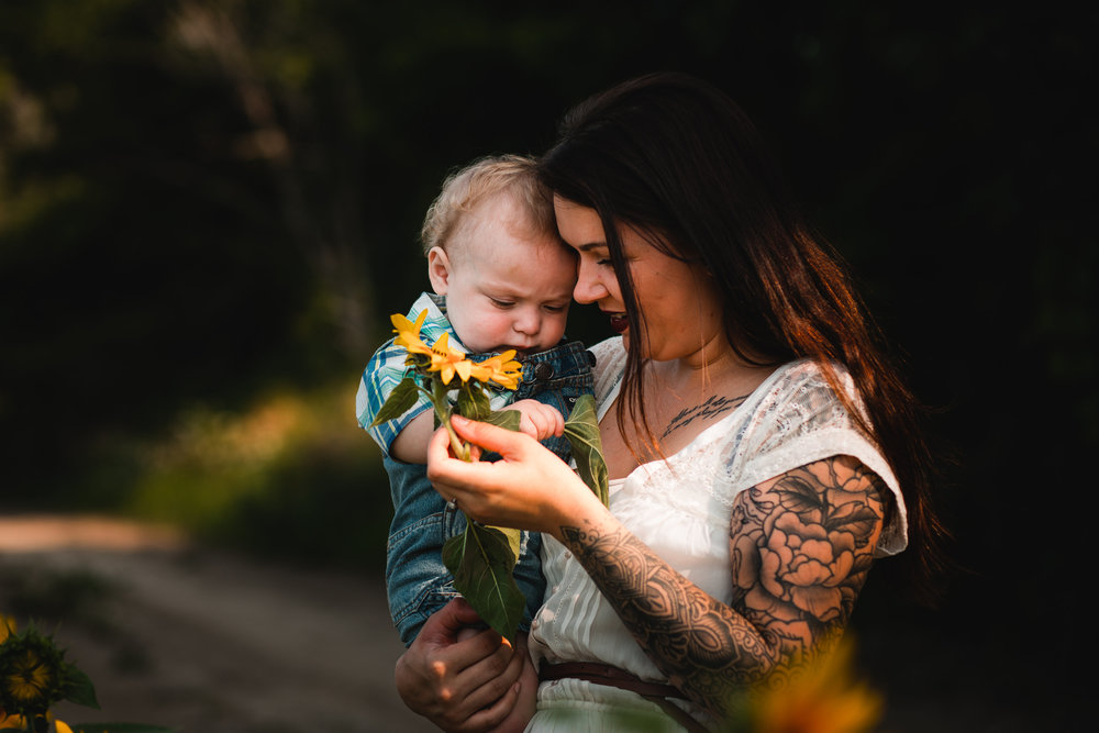 Mom holding baby looking at sunflower