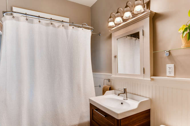 We did a light remodel in the bathroom in 2017, replacing the sink, vanity, and toilet and installing bead board and new baseboard. We kept the original marble hexagon tile on the floor - it is definitely weathered though, showing some pitting and cracks.